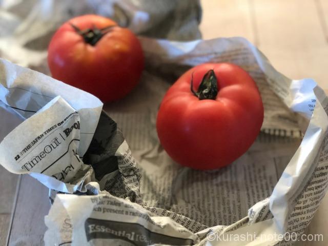 新聞紙にくるまれたトマト